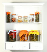 Homemade preserves and some spices on beautiful white shelves — Stock Photo