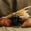 Tankard of kvass and rye breads with ears, on burlap background — Stock Photo #23190996