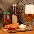 Royalty-Free Stock Photo: Beer and grilled sausages on wooden table on  sackcloth background