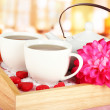 Cups of tea with flower and teapot on wooden tray on table in cafe — Stok fotoğraf