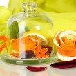 Royalty-Free Stock Photo: Decorative rose from dry orange peel in glass vase on green fabric background
