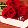 Wedding rings on bible with roses on wooden background — Stock Photo #23192716