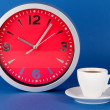Cup coffee and clock on blue background — Photo