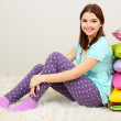 Beautiful young girl with pillows in room — Stock Photo #23193294