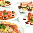 Small portions of food on big white plates close up — Stock Photo