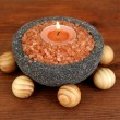 Candle in stone bowl with marine salt, on wooden background - Stok fotoğraf