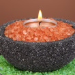 Candle in stone bowl with marine salt, on bamboo mat, on brown background - Foto Stock