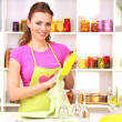 Beautiful young woman wipes clean utensils in kitchen — Стоковая фотография