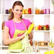 Beautiful young woman wipes clean utensils in kitchen — Stok fotoğraf