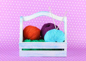 Knitting balls in box on color background — Stok fotoğraf