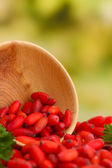 Ripe barberries in wooden bowl with green leaves, on green background — Stock Photo