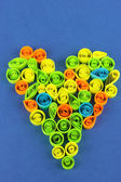 Colorful quilling laid out in form of heart on blue background — Zdjęcie stockowe