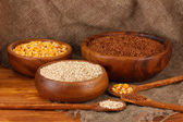 Raw corn,buckwheat and wheat in wooden bowls on table on sackcloth background — Stock Photo