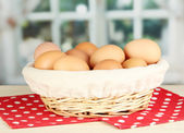 Many eggs in basket on table in room — Stock Photo