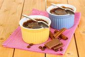 Budyń czekoladowy w miski do pieczenia na drewnianym stole — Zdjęcie stockowe