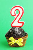 Birthday cupcake with chocolate frosting on green background — Stock Photo