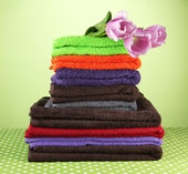 Pile of colorful towels, on green background — Stock Photo