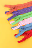 Multicolored zippers on yellow background — 图库照片