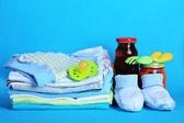 Pile of baby clothes on blue background — Stock Photo