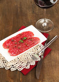Tasty salami on plate on wooden table close-up — Stock Photo