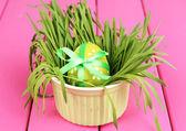 Paskalya yumurtası kase çim pembe ahşap masa üzerinde kapat — Stok fotoğraf