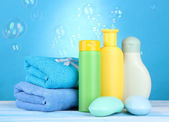 Baby cosmetics, towels and soap on wooden table, on blue background — Stock Photo