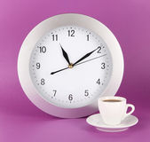 Cup coffee and clock on purple background — Stock Photo