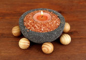 Candle in stone bowl with marine salt, on wooden background — Стоковое фото