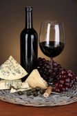 Refined still life of wine, cheese and grapes on wicker tray on wooden table on brown background — Stock Photo
