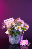 Bouquet of flowers in basket on purple background — Stock Photo