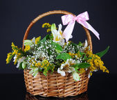 Bouquet of flowers in basket isolated on black — Stock Photo