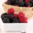 Ripe raspberries and brambles on wooden table — Stock Photo