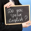 "Young woman holding sign ""Do you speak English?"", on color background — Stock Photo"