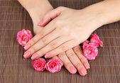 Frau hände mit rosa maniküre und blumen, bambus matten hintergrund — Stockfoto