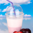 Delicious milk shake with fruit on table on sky background — Foto de Stock