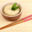 Asian noodles in bowl on bamboo mat — Stock Photo #23325520
