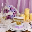 Serving fabulous wedding table in purple and gold color on white and purple fabric background - Stock Photo