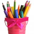 Colorful pencils and felt-tip pens in pink pail isolated on white - Stock Photo