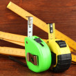 Photo: Tape measure and ruler on wooden background