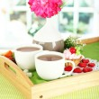 Cups of tea with flower and cake on wooden tray on table in room — Stock Photo #23326412