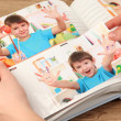 Photos in hands and photo album on wooden table — Stock Photo #23327020