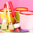 Set for painting: paint pots, brushes, paint-roller, palette of colors on pink background - Stock Photo