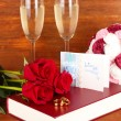 Wedding rings on bible with roses and glasses of champagne on wooden background - Stock Photo