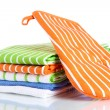 Orange potholder and stack of kitchen towels isolated on white - Stock Photo