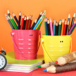 Colorful pencils in two pails with copybooks on table on orange background — Stock Photo #23327624