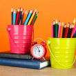 Colorful pencils in two pails with writing-pad on table on orange background — Stok fotoğraf