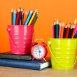 Colorful pencils in two pails with writing-pad on table on orange background — Stock fotografie