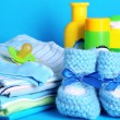 Pile of baby clothes on blue background — Photo