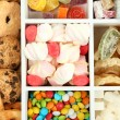Multicolor candies and cookies in white wooden box close up - Stock Photo