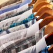 Men's shirts on hangers on beige background — Stock Photo